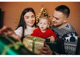 一家人带着小女儿坐在圣诞树旁打开礼品盒_6190872