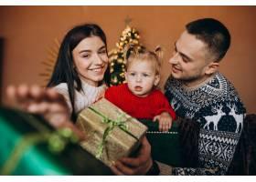一家人带着小女儿坐在圣诞树旁打开礼品盒_6190873