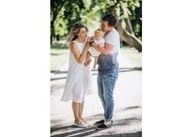 一对年轻夫妇带着他们的小女儿在公园里_5495779