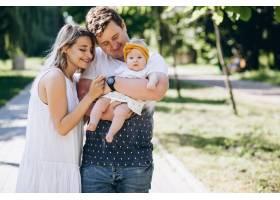 一对年轻夫妇带着他们的小女儿在公园里_5495786