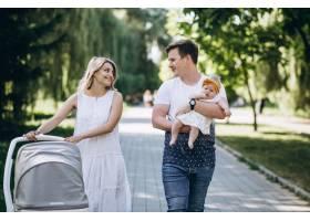 一对年轻夫妇带着他们的小女儿在公园里_5495787