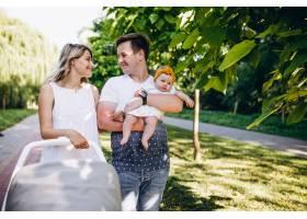 一对年轻夫妇带着他们的小女儿在公园里_5495793