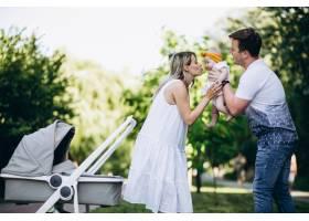 一对年轻夫妇带着他们的小女儿在公园里_5495794