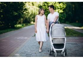 一对年轻夫妇带着他们的小女儿在公园里_5495795