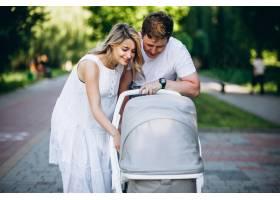 一对年轻夫妇带着他们的小女儿在公园里_5495796