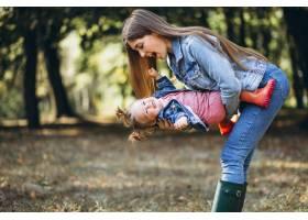 一位年轻的母亲带着她的小女儿在秋天的公园_5852210