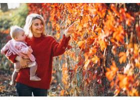 一位年轻的母亲带着她的小女儿在秋天的公园_6255256