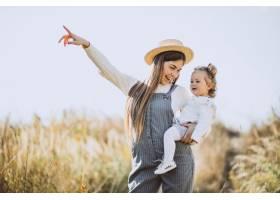 一位年轻的母亲带着她的小女儿在秋天的田野_5852245
