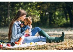一位年轻的母亲带着她的小女儿在秋季公园野_5852229