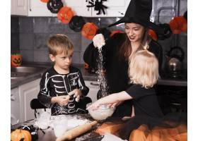 一位母亲和她的孩子们做万圣节饼干的前景_5481618