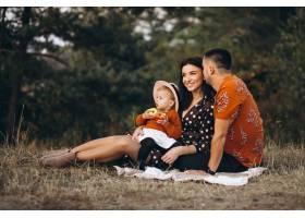 一家人带着他们的小女儿在田野里野餐_5915055