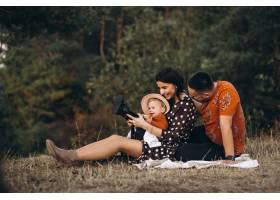 一家人带着他们的小女儿在田野里野餐_5915056