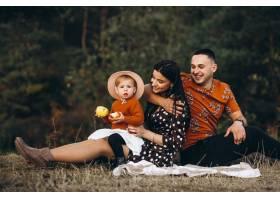 一家人带着他们的小女儿在田野里野餐_5915058