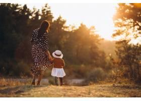 一家人带着他们的小女儿在秋天的田野里_5915046
