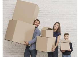 父母和孩子拿着纸箱_6394325