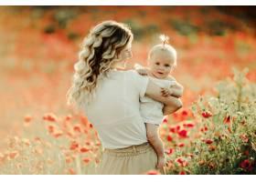 花田里的一名妇女对着婴儿微笑_5697707
