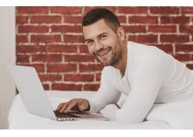 英俊的成年男性使用笔记本电脑_6394886