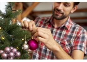 特写装饰圣诞树的快乐男子_5751189