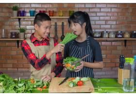 青少年情侣和女孩在厨房用红砖墙做饭时互_5601717