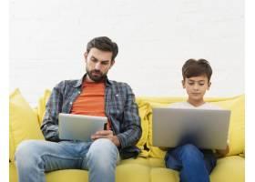 父亲看平板电脑儿子在笔记本电脑上工作_6037453