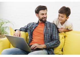 父亲和可爱的孩子在看笔记本电脑_6037454