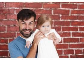 父亲抱着婴儿背景是砖头_6071188