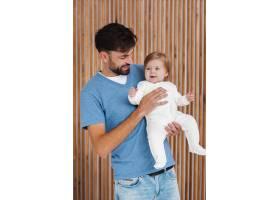 父亲抱着木质背景的婴儿_6071148