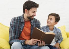 父亲拿着一本书看着他的儿子_6037294
