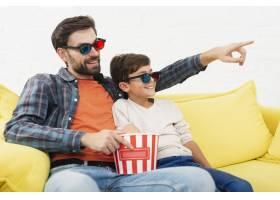 父亲拿着爆米花和儿子一起看电影_6037470