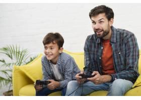 父子俩在游戏机上玩耍_6037389
