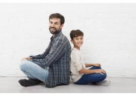 父子俩坐在地板上看着摄影师_6037308