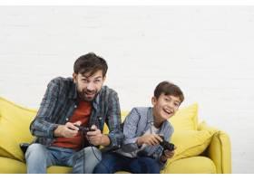 父子俩坐在沙发上玩游戏机_6037402