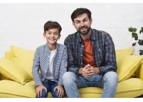 父子俩坐在沙发上看着摄影师_6037323