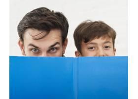 父子俩用一本蓝色的书遮住脸_6037306
