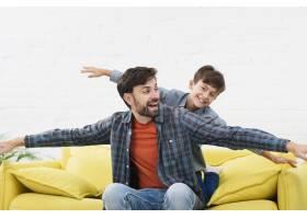 有趣的父子俩在沙发上玩耍_6037412