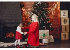 母亲和可爱的女儿在家里穿着一件红色连衣裙_5910944