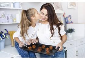 母亲和女儿拿着一个装有松饼的托盘_5809779