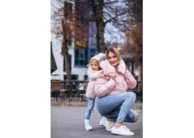 母亲和她的小女儿穿着暖和的衣服在街上_6214108