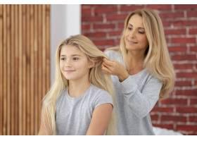 母亲给女儿整理漂亮的头发_5881572