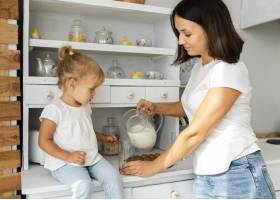母亲给她的小女儿倒牛奶_5918544