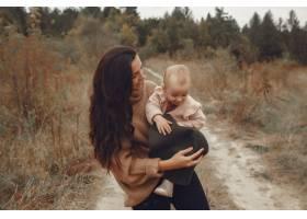 母亲带着小女儿在秋天的田野里玩耍_6239297