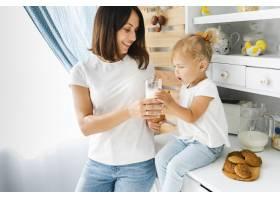 母亲把一杯牛奶递给女儿_5918564