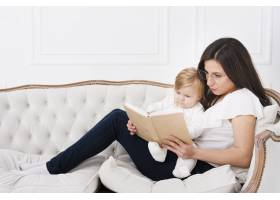 母亲抱着婴儿坐在沙发上看书_6071197