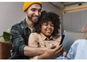 幸福的年轻夫妇看着平板电脑_6121101