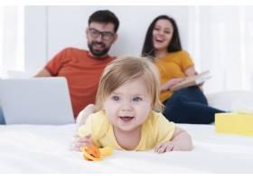 幸福的父母和躺在床上的婴儿_6071163