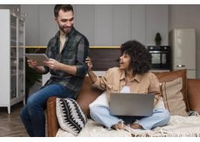 快乐的女人坐在沙发上看着她的男朋友_6121159