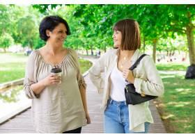 快乐的年轻女子和她的母亲在公园里聊天和散_5259840