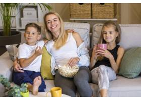 快乐的母亲和她的孩子们吃爆米花_6321736
