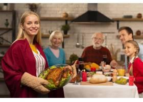 感恩节餐桌上的几代家庭和母亲端来火鸡_5682530