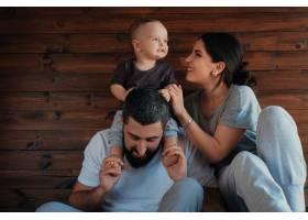 宝宝躺在爸爸的肩膀上和妈妈一起玩耍_5588258